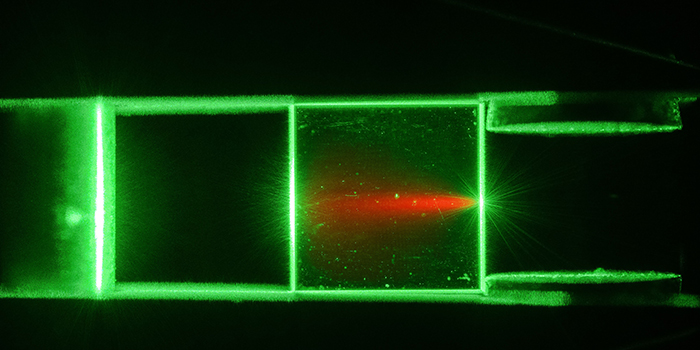 Photo: Jonas Neergaard-Nielsen and Sepehr Ahmadi. A diamond illuminated with green laser light flouresces red light.