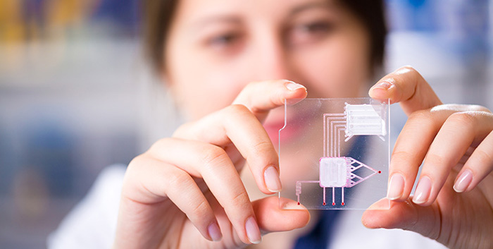 Female researcher showing a lab-on-a-chip device